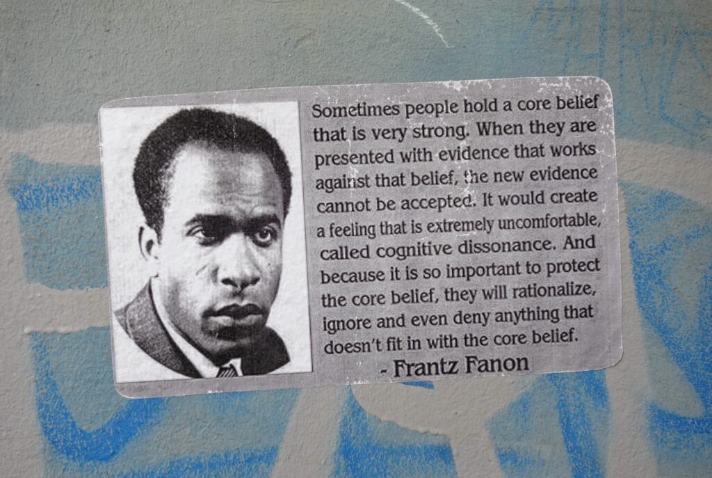 Poster on a wall with quote of Frantz Fanon. Foto: txmx 2. (CC BY-NC-ND 2.0).