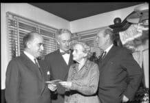 Hans Kirk er tilstede sammen med forfatteren H.C. branner, mens Agnes Henningsen får overrakt Henri Nathansens mindelegat af højesteretssagfører Poul Melchior. Foto: Taget i 1960 af Janne Woldbye (1923-), pressefotograf. (CC BY-NC-ND 4.0).