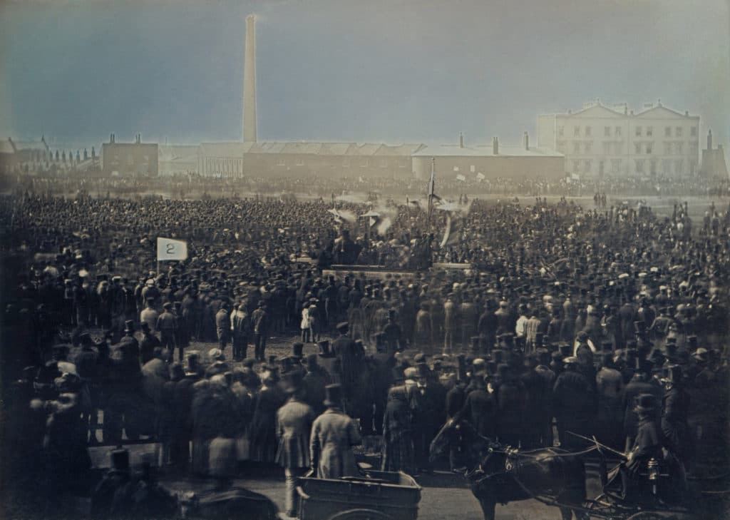 View of the Great Chartist Meeting on Kennington Common. (on 10 April 1848). This daguerreotype, purchased by Prince Albert, records the immense crowds at one of the Chartist rallies held in South London in 1848. Calling for political reform, and spurred on by the recent February Revolution in France, the Chartist movement was seen by many as a terrifying threat to the established order. Fears were so great that on the eve of the meeting pictured, the Duke of Wellington stationed troops across London and the royal family were removed to Osborne House on the Isle of Wight. Photo: Daguerreotype by William Edward Kilburn (1818 - 1891), restored by Bammesk. Public Domain.