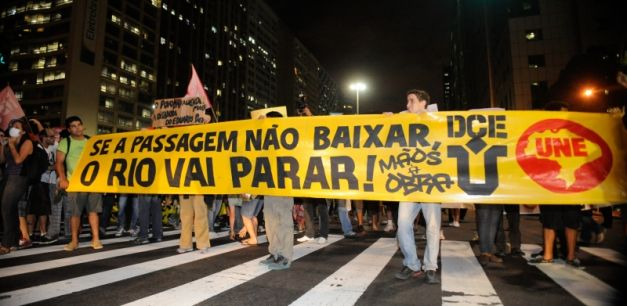 """People protesting in the streets of Rio de Janeiro. The sign reads """"Se a passagem não baixar, o Rio vai parar!"""", which translates to """"If the fare doesn't drop, Rio is going to stop!"""" (Kilde: Wikipedia)"""