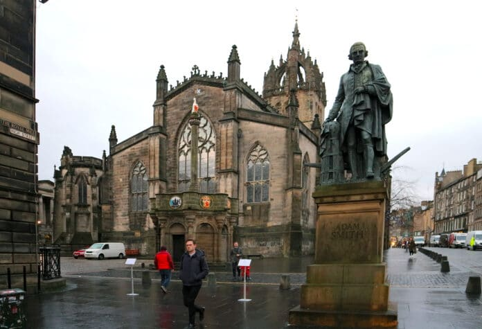 Adam Smith statue in Edinburgh's High Street with St. Giles High Kirk behind. Photo taken 23 November 2018 by Andraszy. (CC BY-SA 4.0).
