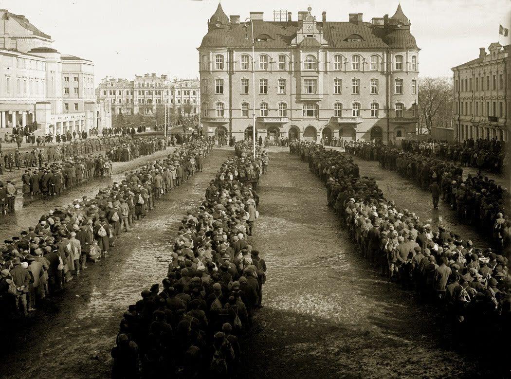 10.000 tilfangetagne rødgardister i Tampere 6. april 1918. Det italienske flag flyver på taget af Selins hus til højre og det svenske flag i Sumelius hus i baggrunden. Fotograf E. A. Bergius. Museum Center Vapriikki fotoarkiv. (CC BY 2.0).