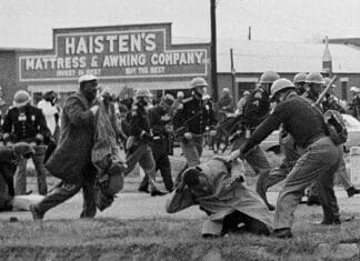 Bloody Sunday. In this March 7, 1965, file photo, a state trooper swings a billy club at John Lewis, right foreground, chairman of the Student Nonviolent Coordinating Committee, to break up a civil rights voting march in Selma, Ala. Lewis sustained a fractured skull. Lewis, who carried the struggle against racial discrimination from Southern battlegrounds of the 1960s to the halls of Congress, died Friday, July 17, 2020. (AP Photo/File). Photo: bswise. (CC BY 2.0).
