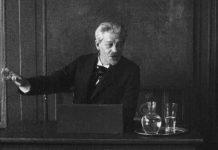 """Screenshot fra den danske stumfilm """"Professor Georg Brandes paa Universitetets Katheder"""" med Georg Brandes, der taler på Københavns Universitet i 1912. Fotograf: Ukendt. Public Domain."""