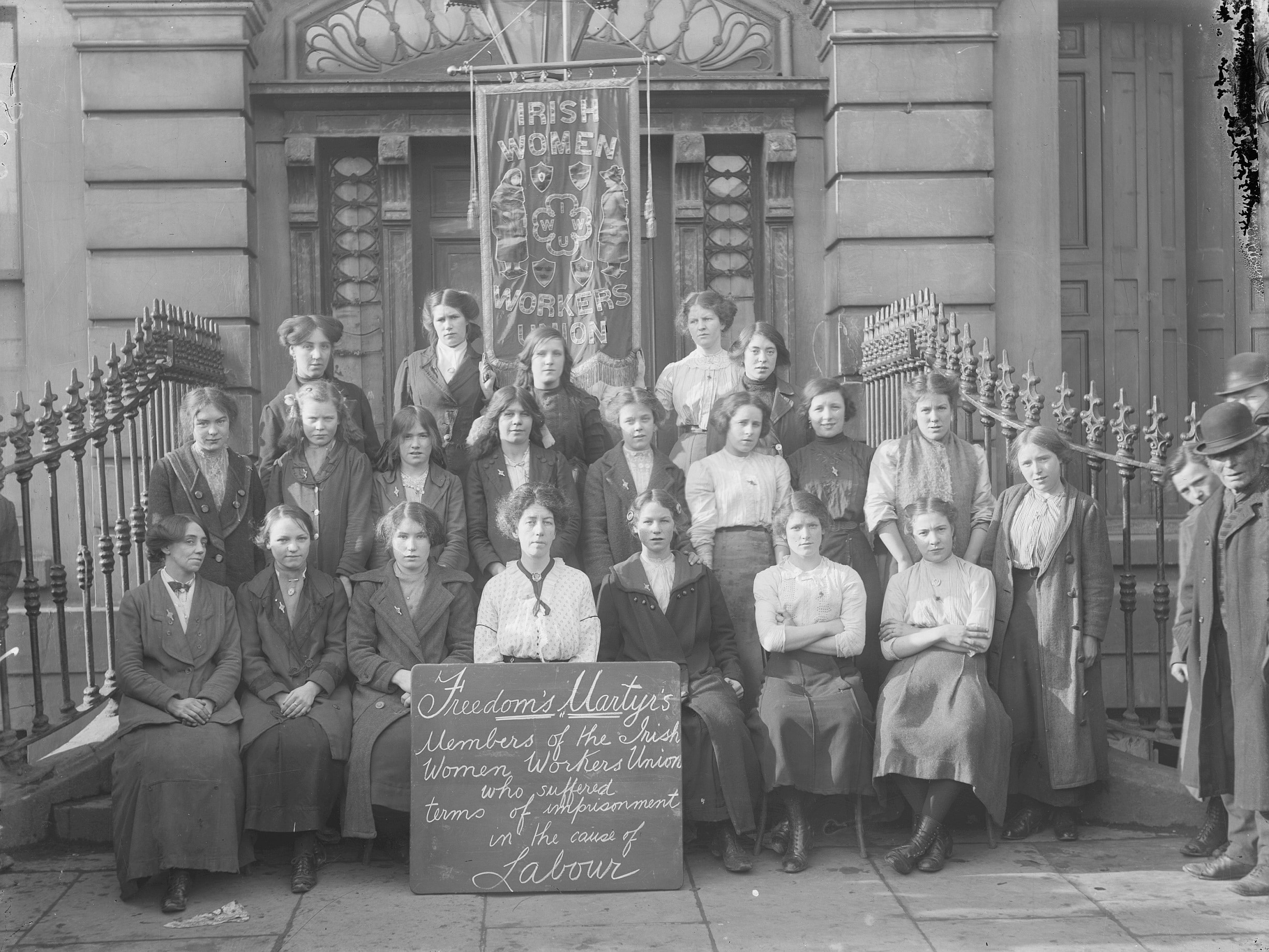 Members of the Irish Women's Workers' Union on the steps of Liberty Hall, c. 1914. The Union was founded in 1911.Text: IRISH WOMEN WORKERS UNION - Freedom's Martyr's : Members of the Irish Womens Workers Union Who suffered terms of imprisonment in the cause of Labour. Photo: Taken ca. 1914. Collection: National Library of Ireland on The Commons. No known copyright restrictions.