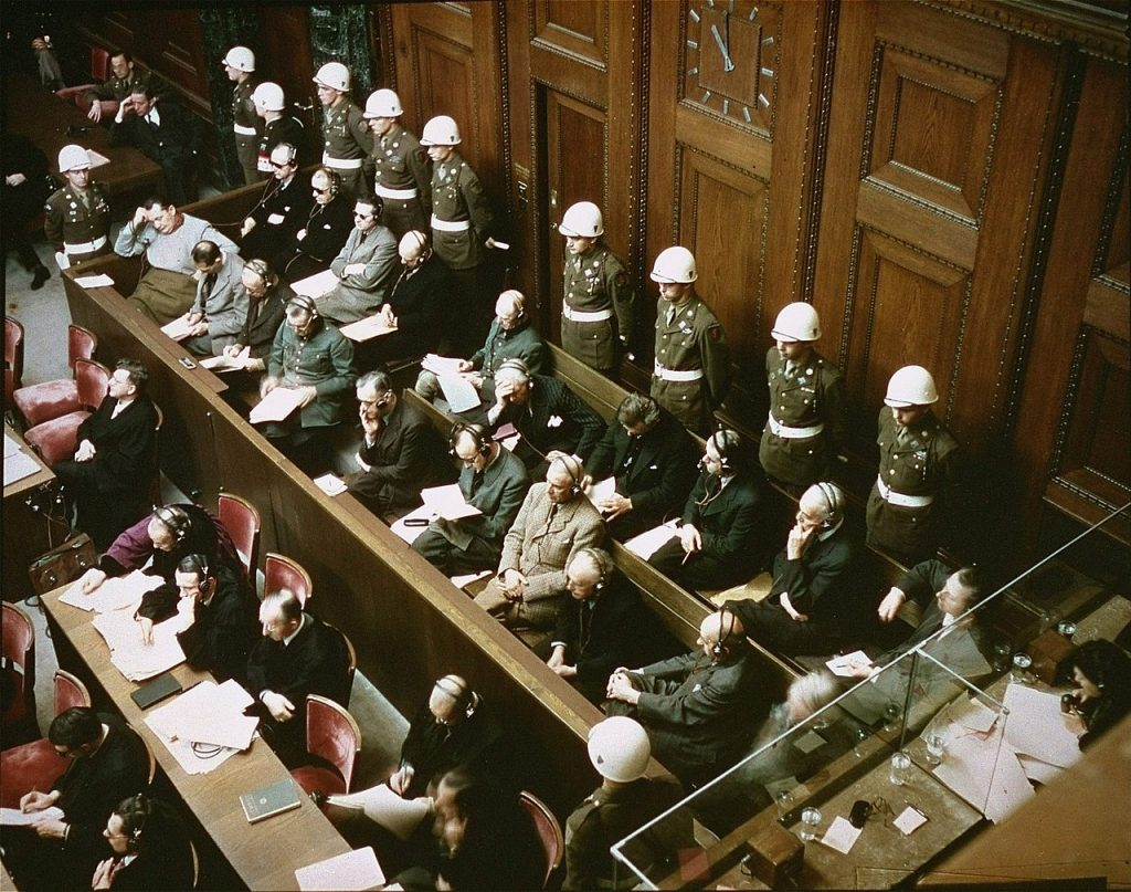 View of the defendants in the dock at the International Military Tribunal trial of war criminals in Nuremberg, Bavaria, Germany. Date: November 1945 Source: ushmm.org Author: Raymond D'Addario. Public Domain.