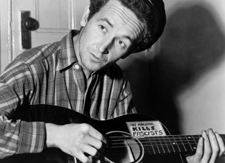Woody Guthrie playing a guitar that has a sticker attached reading: This Machine Kills Fascists. Photo: Taken 8 March 1943 by Al Aumuller. Collection: New York World-Telegram and the Sun, Library of Congress. Public Domain.
