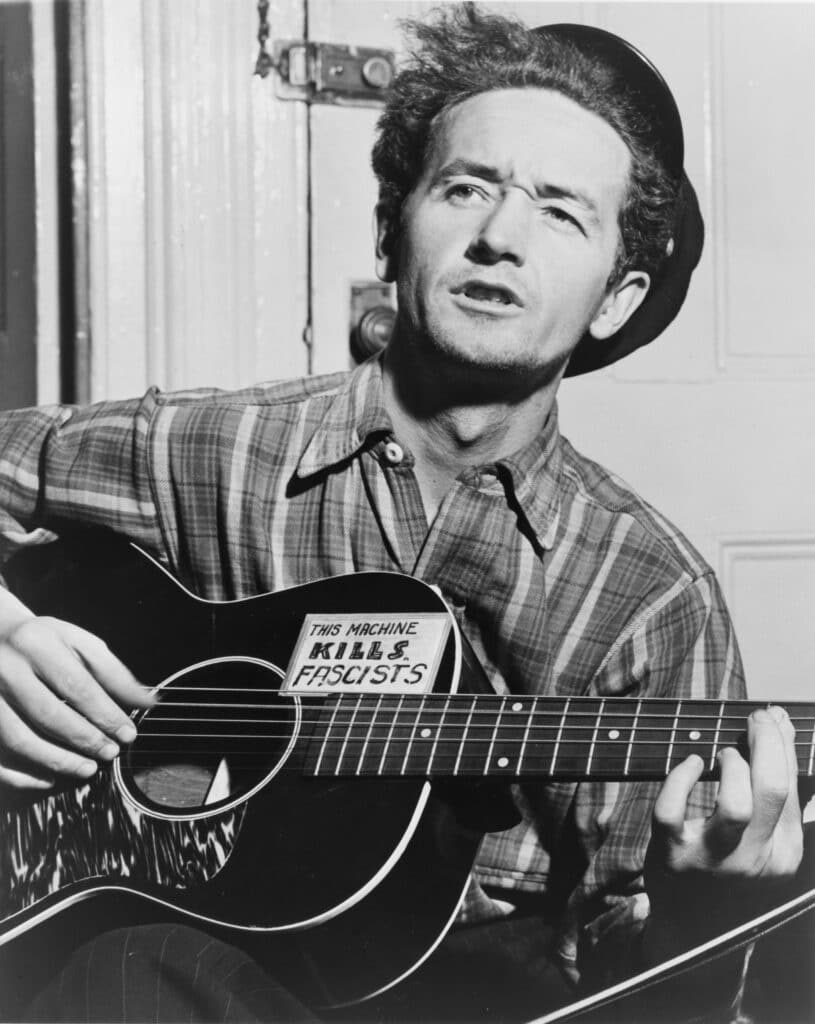 Woody Guthrie with his guitar. Photo: Taken 8 March 1943 by Al Aumuller. Collection: New York World-Telegram and the Sun, Library of Congress. Public Domain.