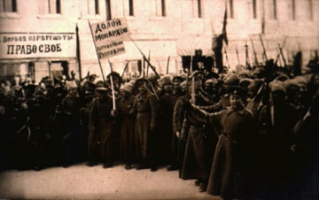 """A Soviet revolutionary postcard from the 1917 Russian revolution. Soviet fighters are shown cheering on a street. In the background is a store that used to say in Russian, """"Watches, gold and silver."""" The has now been altered to read, """"Struggle for your rights."""" Also a flag that before was a solid color now reads, """"Down with the monarchy - long live the Republic!"""". Photo: Unknown Soviet photographer. Public Domain."""