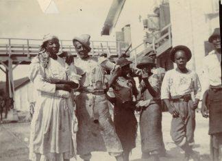 En ældre mand og en kvinde fotograferet sammen med tre drenge og en anden, yngre, mand, på Centralfaktoriets Saftstation, Skt. Croix, 1903. I baggrunden ses en bro, trappeopgang og en bygning. Til venstre yderst i billedet ses et muldyr. Fotograf : Ukendt. Tekst: Henriette Gavnholdt Jacobsen/M/S Museet for Søfart. (CC-BY-NC-SA).