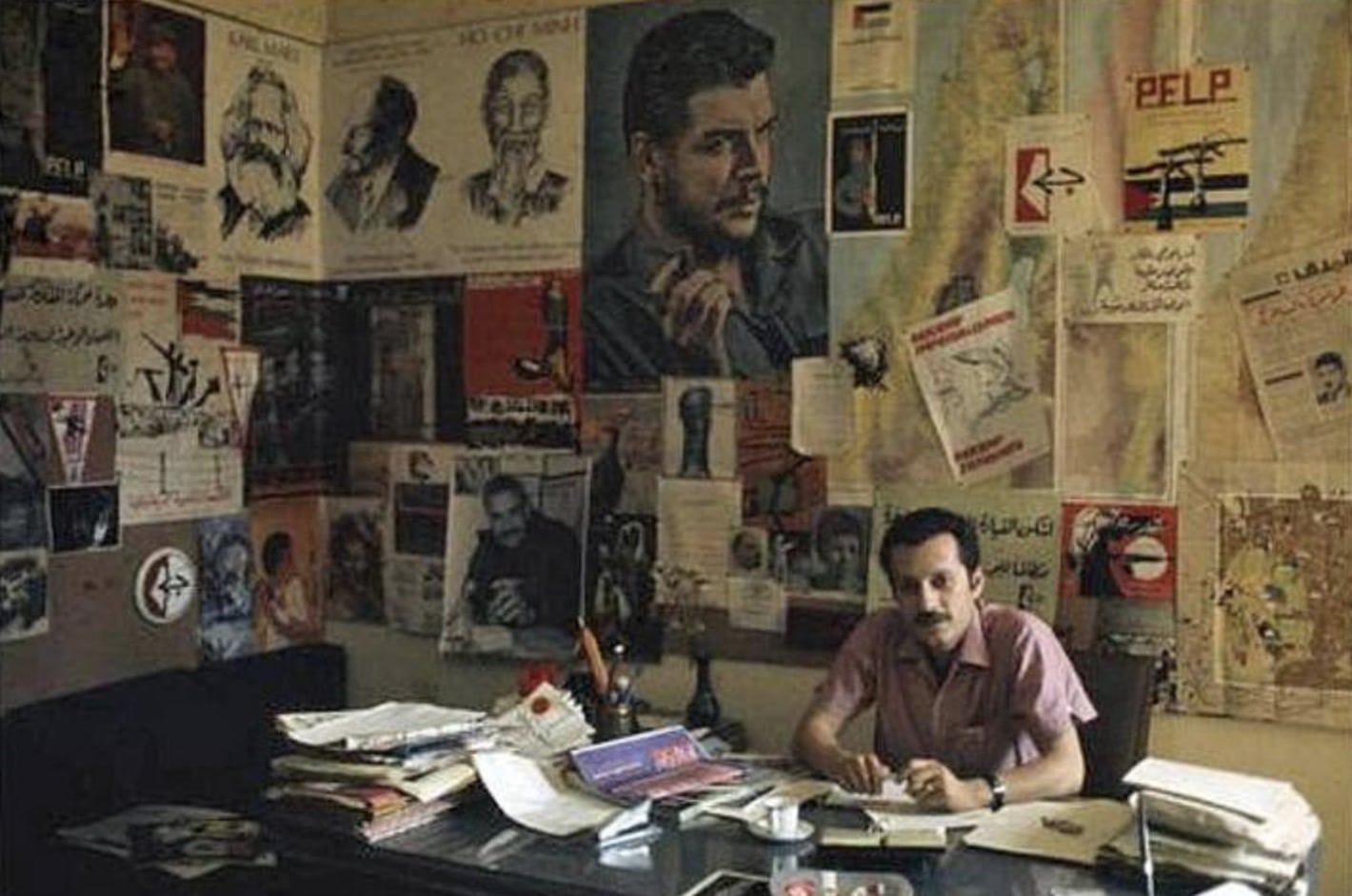 """Ghassan Kanafani in the office in Beiruth. Right above the head of Ghassan Khanafani there is a poster from the Danish organisation KUF, made by Madsen - the poster can be seen in bottom of the section """"PFLP-dokumenter på dansk"""" - PFLP-documents in Danish. Photo: Taken circa 1970 by Bruno Barbey (1941–2020), Moroccan-born French photographer. (CC0 1.0)."""